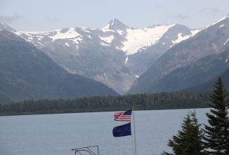 US and Alaska flags and glacier